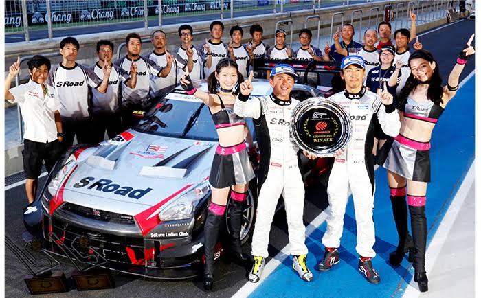 ④専門学校卒業後は3年間レーシングカーのメカニックをしていました。タイで優勝した時の写真です。