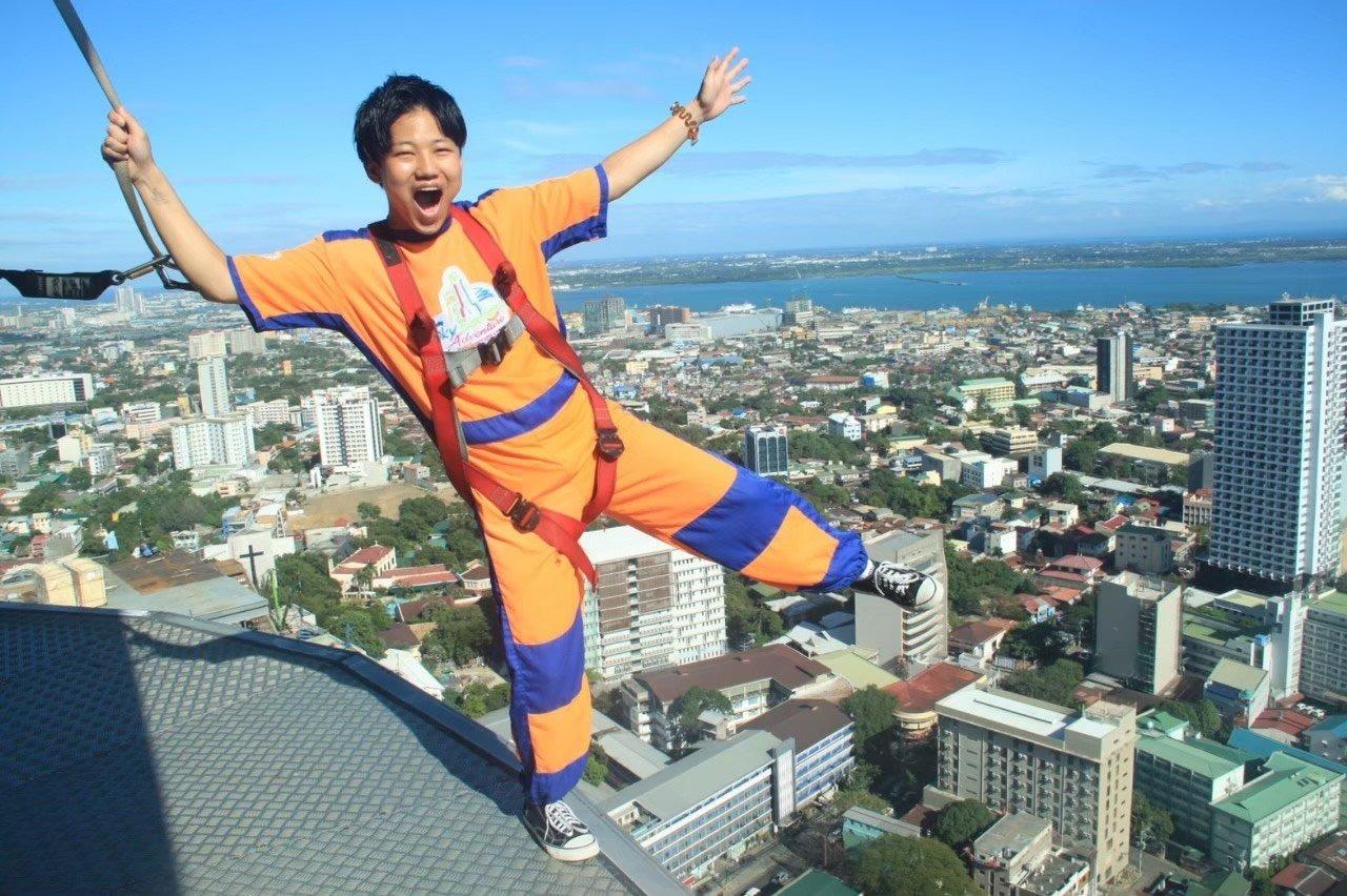 フィリピンで高いビルをあるいてる山田